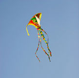 Kite flying in blue sky. Colorful acrobatic kite flying in blue sky Stock Images