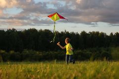 Kite flying. European child having fun flying a kite in the nature.  the boy launches a kite. The boy in a yellow t-shirt with a stock photo