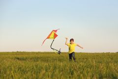Kite flying. European child having fun flying a kite in the nature. the boy launches a kite. The boy in a yellow t-shirt with a. Kite flying. European child stock photography