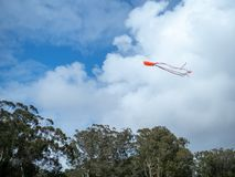 Kite flying high in the sky with parting clouds royalty free stock photos