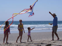 KITE FLYING. A man tries to get a kite aloft for a group of children at Martinique Beach on the Eastern Shore of Nova Scotia Royalty Free Stock Photo