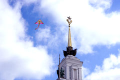Kite flying in the sky above the spire of the building Stock Photography
