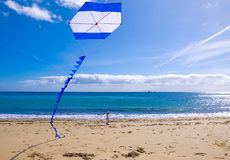 Kite flying in sky with clouds near the sea Stock Images