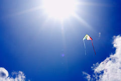 Kite flying in sunlit sky. Colorful kite flying in sunlit blue sky Royalty Free Stock Images