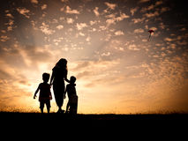 Kite flying at sunset. In silhouette, a woman with two young children flying a kite in the sky with a colorful sunset as a backdrop Stock Photo