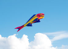 A kite on the form of fish floating above the clouds Stock Photos