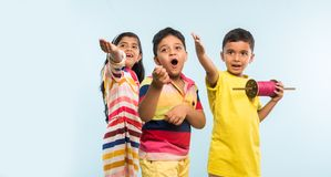 3 indian kids flying kite, one holding spindal or chakri Stock Photos
