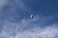 Kite of rainbow colors on a blue sky with light white clouds Royalty Free Stock Photo