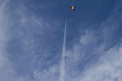 Kite of rainbow colors on a blue sky with light white clouds Stock Photography