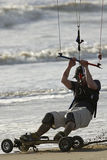 Kite Skateboarder Close-up 2. A kite skateboarder rides the sand with his Royalty Free Stock Photos