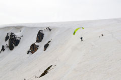 Kite skier flying off the mountain ridge Stock Photography