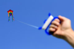 Kite in the sky. Multicolored kite high in clear blue sky, string holding in male hand, focused on kite Stock Images