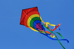 Kite in the sky. Multicolored kite with tail in clear blue sky Royalty Free Stock Photo