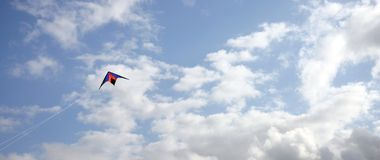 Kite in the sky. Colorful kite in a cloudy summer sky Royalty Free Stock Image