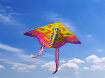 Kite in the sky. Brightly coloured kite is flying in the blue sky Royalty Free Stock Photo