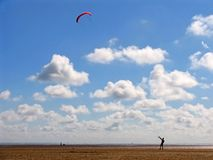 Kite in Sky. Lonesome figure flying kite over barren landscape, on beautiful day with blue sky and white clouds Stock Photo