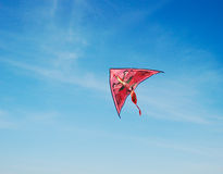 A kite in the sky. A pink kite high in the blue sky Royalty Free Stock Photo