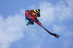 Kite in the Sky. Colorful kite flying high with blue sky and white clouds Stock Images