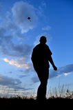 Kite in the sky. Silhouette of a man, view from the ground stock photography