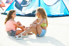 Kite surf teen girls talking in summer beach sitting Stock Photography