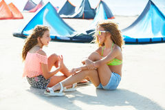 Kite surf teen girls talking in summer beach sitting Royalty Free Stock Images