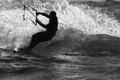 Kite Surfer. Silhouette against white water spray royalty free stock images