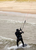 Kite surfer comes onto the beach Royalty Free Stock Images