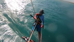 Kite surfer is gliding on water, turning, water splash, view from the slings