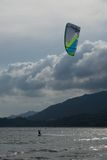 Kite surfer with green and blue kite Royalty Free Stock Images