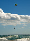 Kite-surfer hovering above waves Stock Images