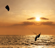Kite surfer jumping from the water. At sunset ocean Royalty Free Stock Images
