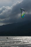 Kite surfer and kite backlit against clouds Royalty Free Stock Photos