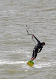 Kite surfer performing stunts. Photo of a male kite surfer performing one handed stunts on the coast of whitstable in kent england.photo taken 17th june 2014 and stock image