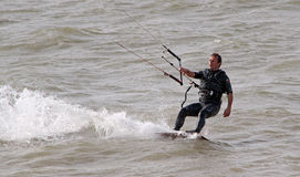 Kite surfer performing stunts. Photo of a male kite surfer performing one handed stunts on the coast of whitstable in kent england.photo taken 17th june 2014 and stock photography