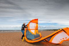 Kite surfer  is preparing his kite on a windy cold day Royalty Free Stock Photo