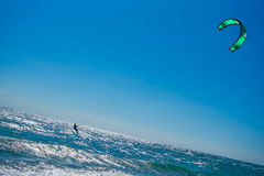 Kite surfer rides the waves. A kite surfer rides the waves board, water, surfboard, surf royalty free stock photography