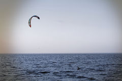 Kite surfer rides on the waves under parachute Stock Image