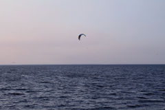 Kite surfer rides on the waves under parachute Stock Photos