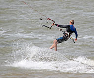 Kite surfer stunts at sea. Photo of a male kite surfer performing stunts at sea off the coast of whitstable in kent on 17th june 2014.photo ideal for kite stock images