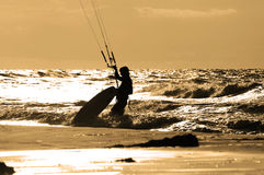 Kite surfer at sunset. Kite boarder on beach in sunset is moving his board into the water Stock Images