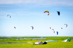 Kite surfers in sea. Scenic view of group of kite surfers in sea with green field in foreground royalty free stock photography