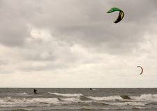 Kite surfers. Two kite surfers at sea on a cloudy day royalty free stock photography