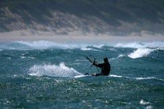 Kite surfing. Man kite surfing in rough waters stock image