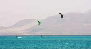 Kite surfing. Two kite surfers, blue sea and mount background Stock Image