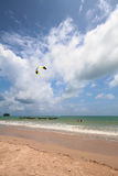 Kite surfing on a tropical beach. Next to long tail boats in the Andaman Sea, Nai Yang, Thailand Royalty Free Stock Photography