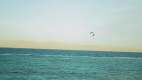Kite surfing in beautiful clear water in Dahab Egypt. Exploring the blue water with mountains in the background and
