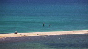 Kite surfing on blue sea surface. Kite surfing. surfers on blue sea surface. Shot from high point of view stock footage