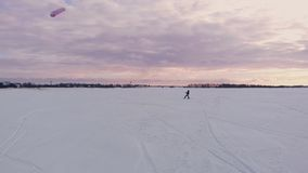 Kite surfing on a frozen lake in winter at sunset.  stock video