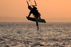 Kite surfing girl in swimsuit with kite in sky on board in sea jumping freestyle trick move. Recreational activity, water. Sports, action, hobby and fun in stock photo