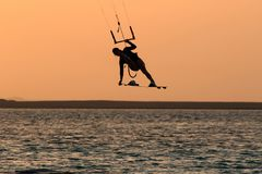 Kite surfing girl in swimsuit with kite in sky on board in sea jumping freestyle trick move. Recreational activity, water. Sports, action, hobby and fun in royalty free stock image
